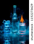 Small photo of Two, blue and red shot glasses full of drinks one of wich with ice and second is burning, and a bottle in a smoke on a black background. Conceptual, commercial and advertising photo. Copy space.