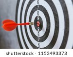 Stock photo red dart arrow hitting in the target center of dartboard 1152493373