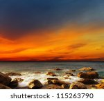 Red Sky Over A Rocky Seashore....