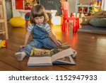 a cute little girl is reading a ...