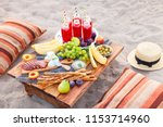 picnic on the beach at sunset... | Shutterstock . vector #1153714960