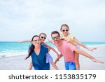 happy family on a beach during... | Shutterstock . vector #1153835179