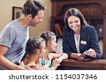 happy family checking in hotel... | Shutterstock . vector #1154037346