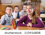 Elementary aged pupils in classroom during lesson - stock photo