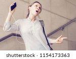 emotional young woman dancing...   Shutterstock . vector #1154173363