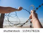 hands open barbed wire outdoors ...   Shutterstock . vector #1154178226