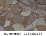 Small photo of Rough multycolored unregular shape Stones floor with white cement between
