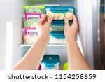 woman placing container with... | Shutterstock . vector #1154258659