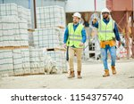 two young men in hardhats and... | Shutterstock . vector #1154375740