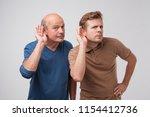 two caucasian men hearing with... | Shutterstock . vector #1154412736