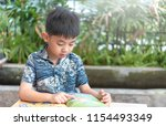 kid boy reading a book at home | Shutterstock . vector #1154493349