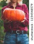 girl holding a pumpkin in her... | Shutterstock . vector #1154548579