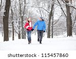 Couple walking and running in winter forest happy and joyful holding hands on romantic date in winter snow forest landscape. Cheerful interracial young couple, Asian woman, Caucasian man. - stock photo
