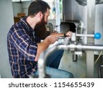 brewery worker cleaning out hop ... | Shutterstock . vector #1154655439