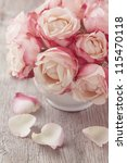 Stock photo pink roses and petals on wooden desk 115470118