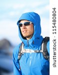 Hiking man - hiker portrait of young male hiker and climber in alpine wear hard shell jacket in high altitude mountain above the clouds. - stock photo