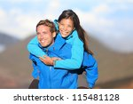 Happy hiking couple piggyback having fun on hike. Fresh young blissful interracial couple. Asian woman hiker and Caucasian man hiker. - stock photo