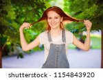 redhaired girl twists her hair  | Shutterstock . vector #1154843920