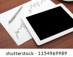 finance table on a wooden table ... | Shutterstock . vector #1154969989