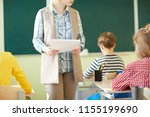 young teacher moving among row... | Shutterstock . vector #1155199690