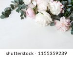 Styled stock photo. Decorative still life floral composition. Wedding or birthday bouquet of pink and white peony flowers and eucalyptus branches. White table background. Flat lay, top view.