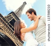 Paris Eiffel tower romantic couple embracing kissing in front of Eiffel Tower, Paris, France. Happy young interracial couple, Asian woman, Caucasian man. - stock photo