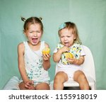 two girls taste sour lemon... | Shutterstock . vector #1155918019