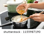 woman adding oil to boiled rice ... | Shutterstock . vector #1155987190