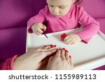 the child paints the nails of... | Shutterstock . vector #1155989113