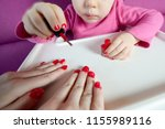 the child paints the nails of... | Shutterstock . vector #1155989116