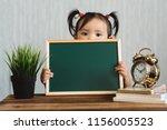 cute asian toddler holding a... | Shutterstock . vector #1156005523