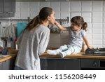 little daughter feeding mother... | Shutterstock . vector #1156208449