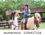cute asian child girl riding a... | Shutterstock . vector #1156417126