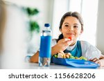 happy little schoolgirl eating... | Shutterstock . vector #1156628206