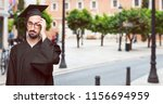 Small photo of graduate bearded man Looking unenthusiastic and bored, listening to something dull and tedious, yawning in utter boredom.