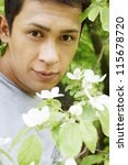 The young man next to a flowering quince bush - stock photo
