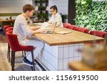 Stock photo view of man and woman sitting with laptops and papers at table in cafeteria having big load of work 1156919500