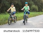 two brothers ride bikes summer... | Shutterstock . vector #1156997533