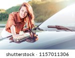 young woman cleaning her car... | Shutterstock . vector #1157011306