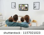 Family Watching Tv On Sofa At...