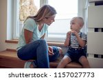 mother playing with her son... | Shutterstock . vector #1157027773