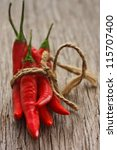 Bunch of chili peppers on an old wooden board. - stock photo