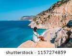 young woman sitting on a rock... | Shutterstock . vector #1157274859
