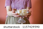 the woman holding and offering... | Shutterstock . vector #1157429590