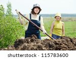 Two women works with animal manure at field - stock photo