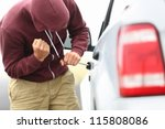 View down the side of a car to a man in a hooded top breaking into a car with a screwdriver in order to steal it - stock photo