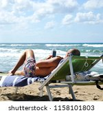 man at the beach lying on the... | Shutterstock . vector #1158101803
