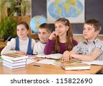 Four schoolchildren aged 11 at the desk in classroom - stock photo