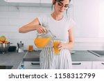 girl pouring orange juice in...   Shutterstock . vector #1158312799
