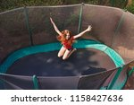 happy teenage girl jumping on... | Shutterstock . vector #1158427636